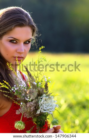 Woman with flowers in a field - stock photo