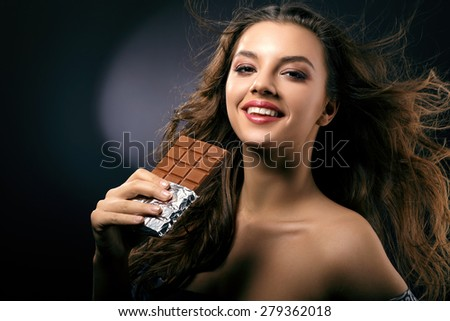 Woman with flowing hair and a chocolate bar in her hand close-up - stock photo
