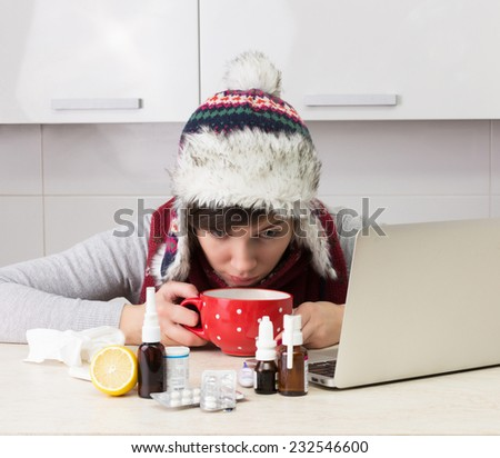 Woman with flu at the laptop - stock photo