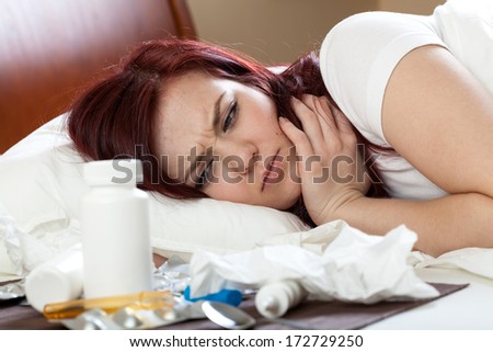Woman with flu lying in bed with medications - stock photo