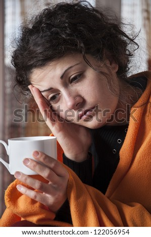 woman with flu symptoms holding a cup in his hand - stock photo