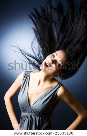Woman with fluttering hair. On dark background. - stock photo