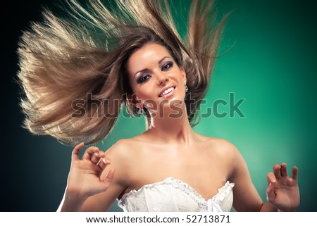 Woman with fluttering hair. On dark green background. - stock photo