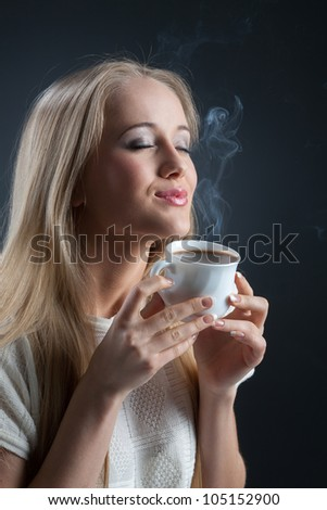 Woman with fresh coffee in hand on a black background