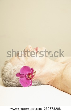 Woman with Fresh Flower Behind Her Ear - stock photo
