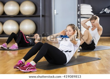 Woman With Friends Doing Situps In Gymnasium