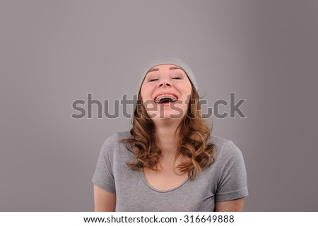 woman with funny face on grey background - stock photo