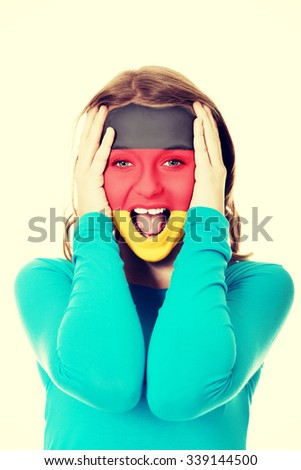 Woman with Germany flag painted on face. - stock photo