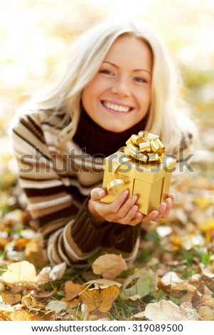 Woman with gift laying on dry autumn leaves - stock photo