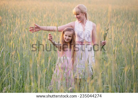 Woman with girl in field of wheat - stock photo