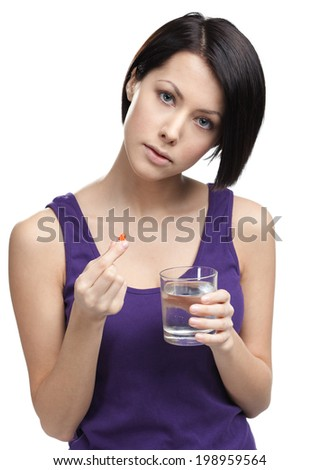 Woman with glass of water takes capsules, isolated on white. Medication routine