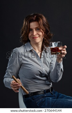 woman with glass of whiskey and cigar on black background  - stock photo