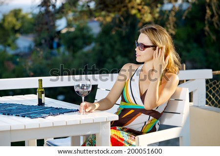 Woman with glass of wine by the sea - stock photo