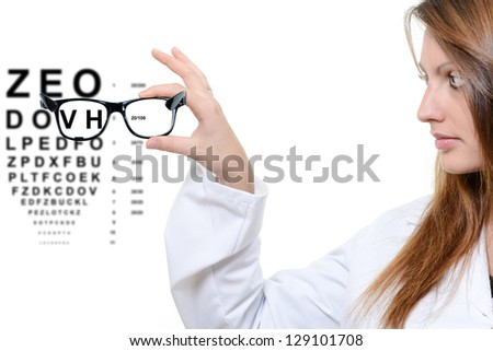 Woman with glasses and snellen eye chart in background - stock photo