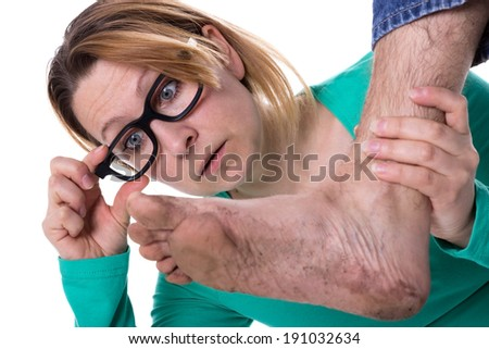Woman with glasses is astonished about a dirty foot