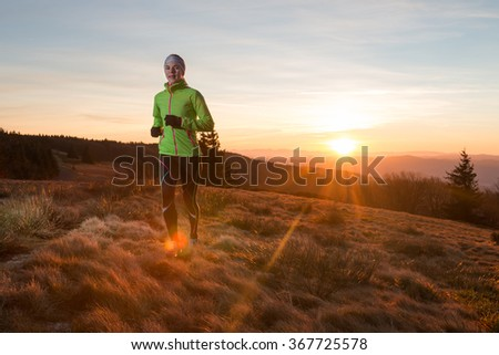 woman with gloves training in the mountains in cold morning with first ray of light of the sunrise  - stock photo