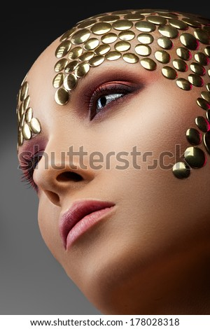 Woman with golden applique on the face on gray background