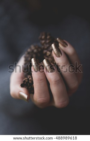Woman with golden nails holding pine cones. Old film look. Selective focus, short depth of field. Old film look.