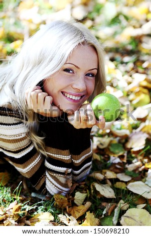 woman with green apple in autumn park - stock photo
