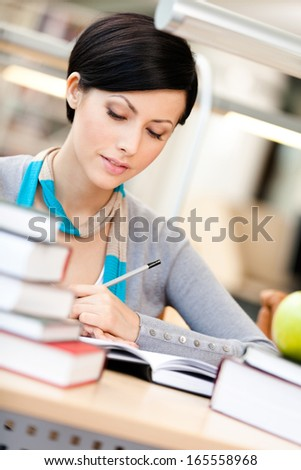 Woman with green apple surrounded with piles of books reads sitting at the table at the library. Academic achievement - stock photo