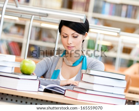 Woman with green apple surrounded with piles of books reads sitting at the table at the library. Information overload - stock photo
