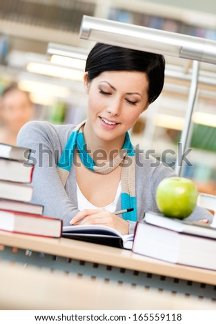 Woman with green apple surrounded with piles of books reads sitting at the table at the library