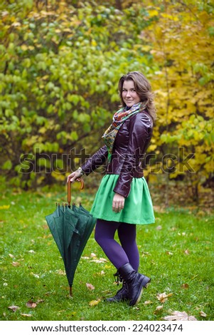 Woman with green umbrella smiling as raining, against green of autumn park - stock photo