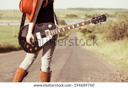 woman with guitar at freeway - stock photo