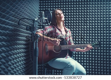 Woman with guitar in recording studio