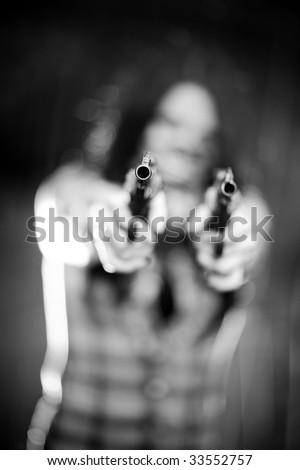 Woman with gun. Shallow dof focus on gun. - stock photo