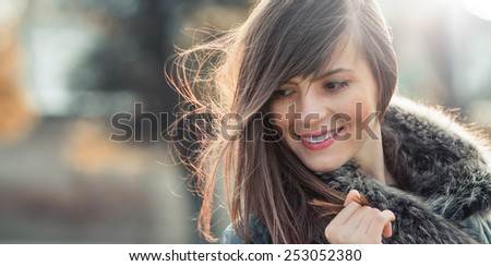 Woman with hair blowing in the wind with a blurred nature background, natural hairstyle. Outdoors with copyspace - stock photo