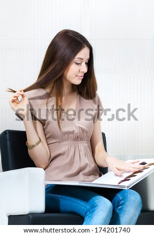 Woman with hair color samples sits in the hairdress salon. Concept of fashion and beauty - stock photo