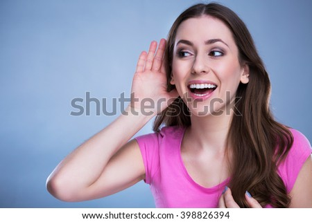 Woman with hand to ear listening  - stock photo
