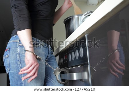 Woman with handcuffs cooking in the kitchen - stock photo