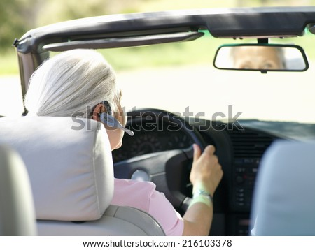 Woman with hands-free device in car, rear view - stock photo