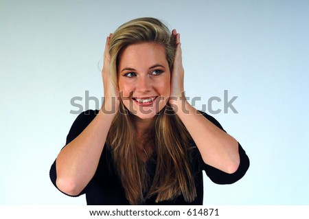 Woman with hands over her ears, smiling and looking to her left. - stock photo