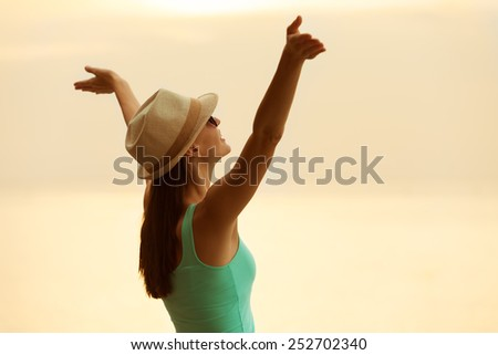 Woman with hands raised in the sunset.  - stock photo