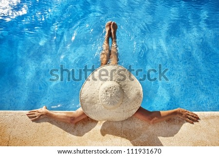 Woman with hat at poolside - stock photo