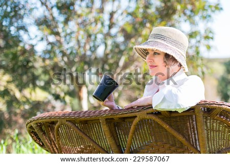 Woman with hat enjoying in nature and looking far