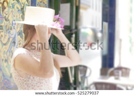 woman with hat in a the street. coffee blurry background
