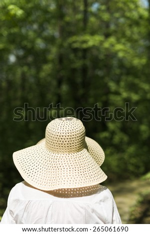 woman with hat in the park - stock photo