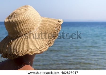 woman with hat protects from sun on the beach, close up