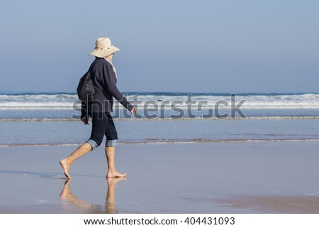 Woman with hat walking along the seashore