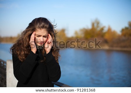 woman with headache in park - stock photo