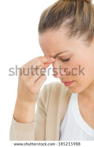 Woman with headache pinching her nose and wincing on white background