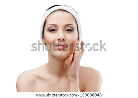 Woman with headband making face moisturizing procedures, isolated on white - stock photo
