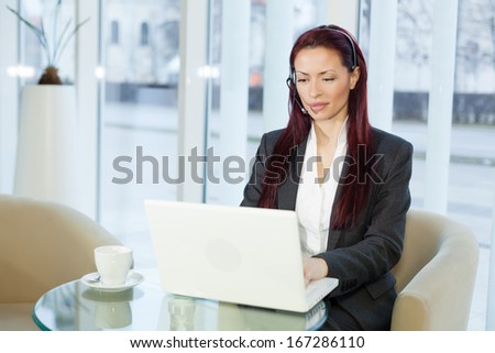 Woman with headphone talking and using a laptop computer