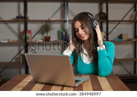 Woman with headphones is sitting at the wood table
