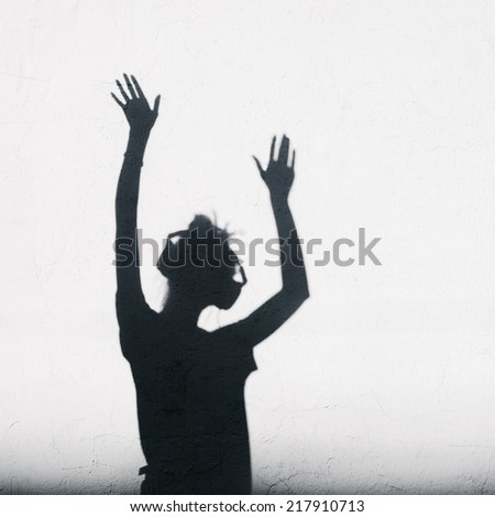 Woman with headphones lifting her hands up. Photo of shadows of dj girl