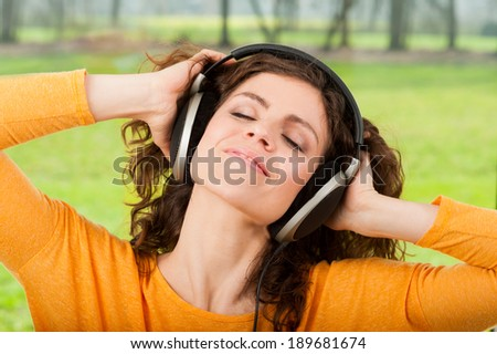 Woman with headphones listening the music . Dancing with nature in the background  - stock photo